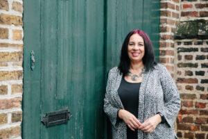 Janet Efere standing in front of a green door